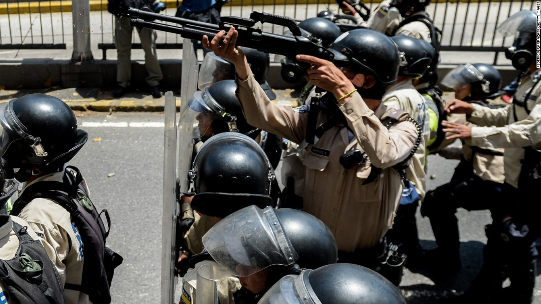 Riot police stand guard at a demonstration in Caracas, Venezuela.