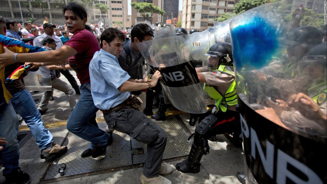 Demonstrators fight on Tuesday, April 4, with national police officers in Caracas, Venezuela.