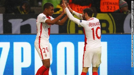 Striker Kylian Mbappe celebrates with Bernardo Silva after scoring the first of his two goals against Dortmund.