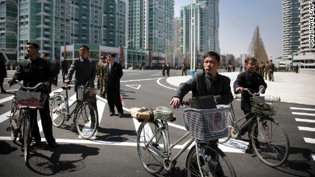 Men wheel their bicycles through the Ryomyong Street complex.