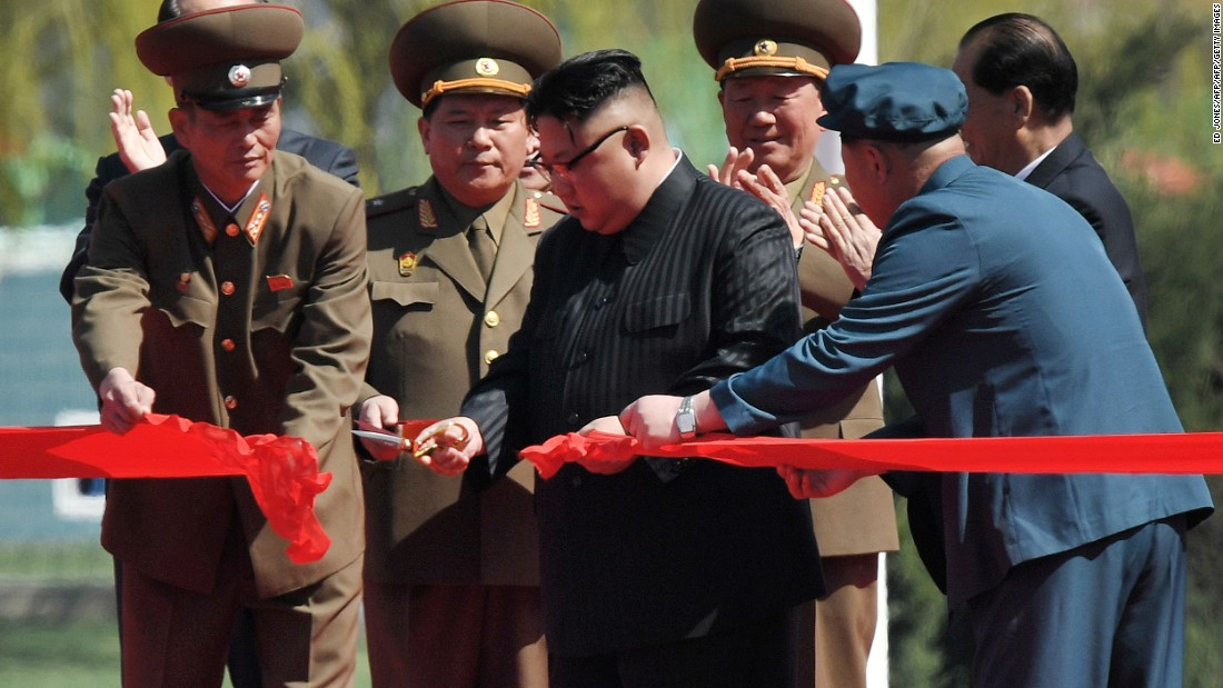 Kim Jong Un cuts a ribbon to mark the opening of the street.