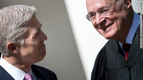 Neil Gorsuch (L) smiles at Supreme Court Justice Anthony Kennedy before taking the judicial oath during a ceremony in the Rose Garden of the White House on April 10.