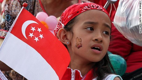 A girl holding the Singapore flag sings along during an event to celebrate Singapore's 44th National Day on August 9, 2009. In his National Day message Singapore Prime Minister Lee Hsien Loong indicated that Singapore's economic contraction in the first half of the year was not as bad as feared and that the country is now in a stronger position than at the start of the year. AFP PHOTO (Photo credit should read AFP/AFP/Getty Images)