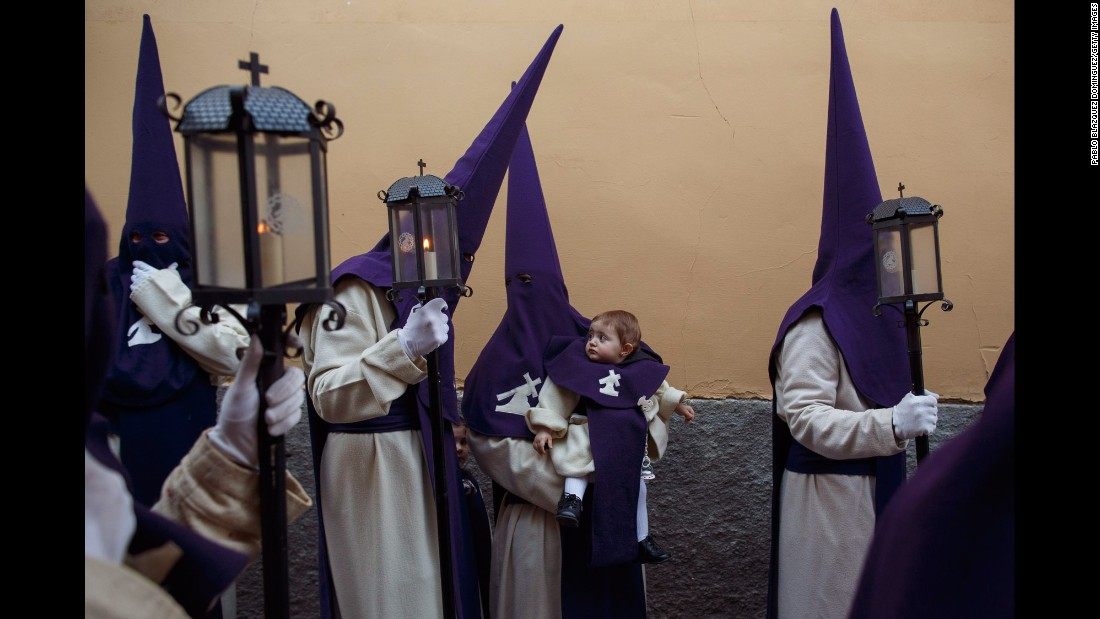 A penitent holds an infant during a Holy Week procession in Zamora, Spain, on Tuesday, April 11.