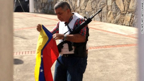 Venezuelan opposition Army General Angel Vivas Perdomo holds a Venezuelan national flag as he remains armed at his house in Caracas on February 23, 2014. Vivas Perdomo resisted being arrested. On Saturday the largest opposition rally took place after almost three weeks of students protests, which left ten people killed. AFP POHOTO / STR        (Photo credit should read STR/AFP/Getty Images)
