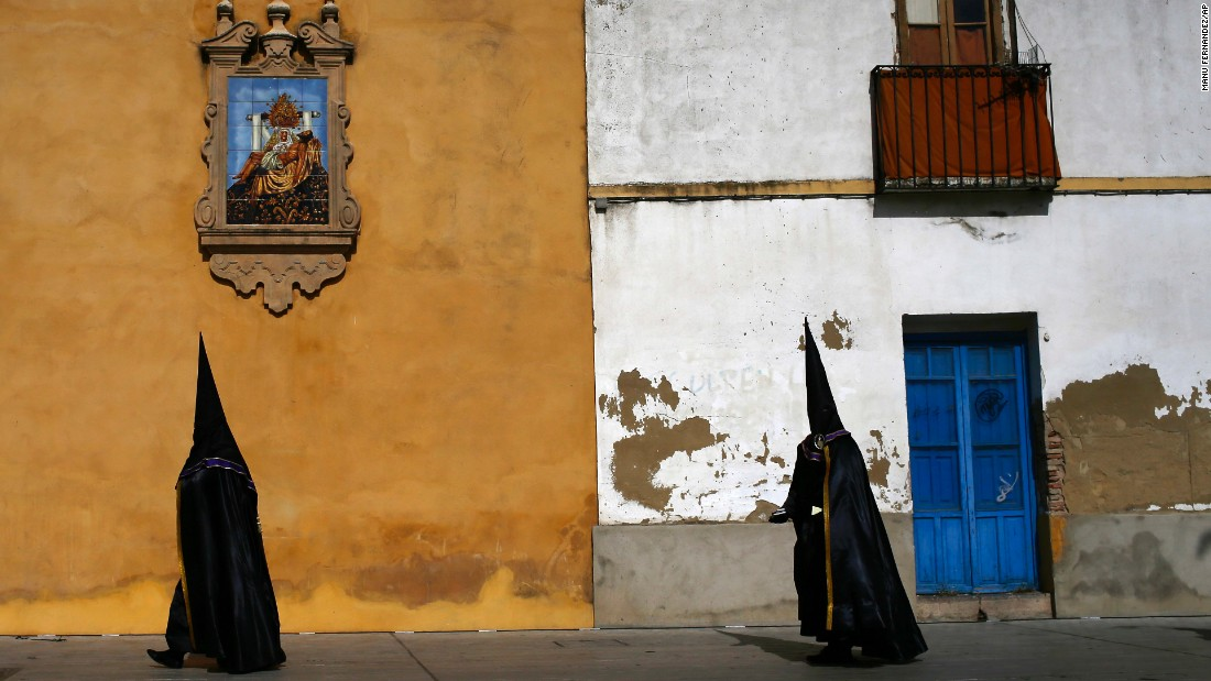 Hooded penitents from the Las Angustias brotherhood take part in a Holy Week procession in Cordoba, Spain, on Thursday, April 13.