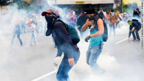 Venezuelan opposition activists clash with riot police during a protest against President Nicolas Maduro's government, in Caracas on April 13, 2017. A 32-year-old man died Thursday after being shot and wounded in a demonstration on April 11, becoming the fifth victim in the protests that began almost two weeks ago. Dozens of people have been injured and more than 100 arrested since April 6, according to authorities. / AFP PHOTO / FEDERICO PARRA        (Photo credit should read FEDERICO PARRA/AFP/Getty Images)