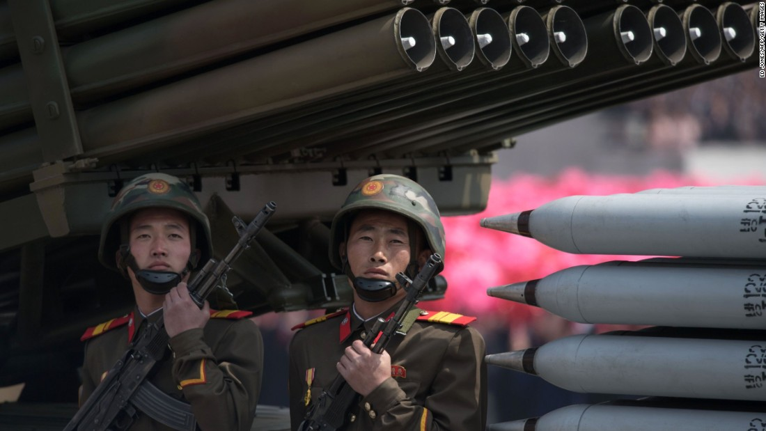 Members of the Korean People's Army ride on mobile missile launchers.