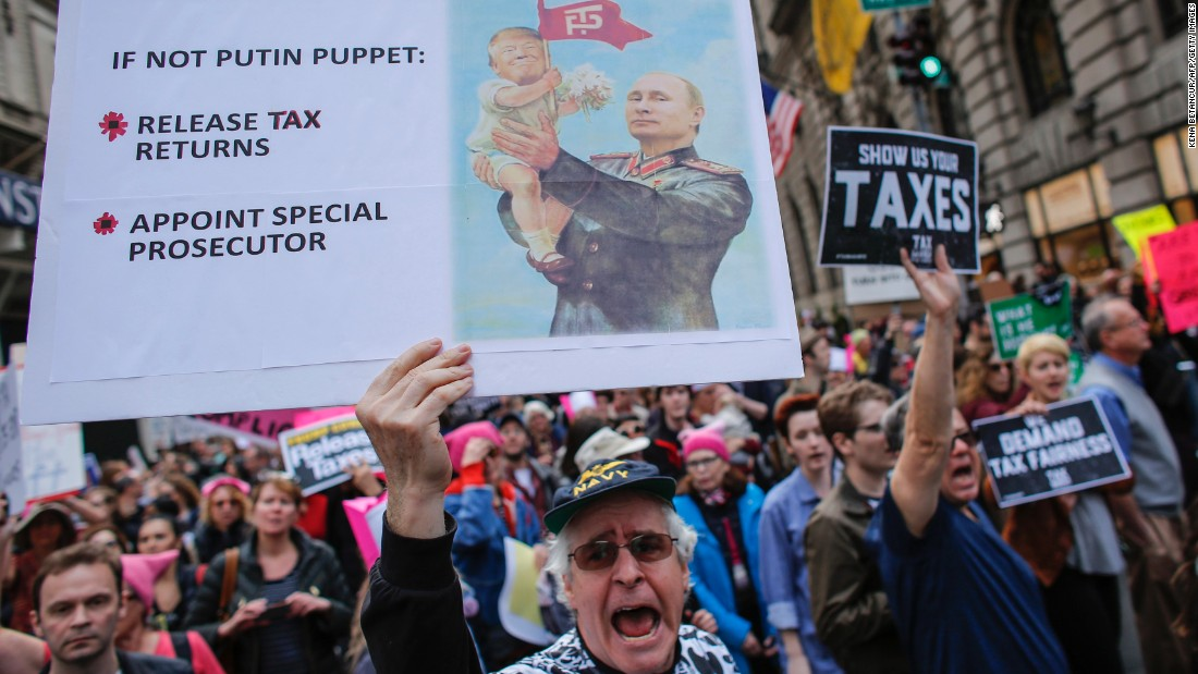 "Protesters pass near Trump Tower in New York during the nationwide ""Tax March."""