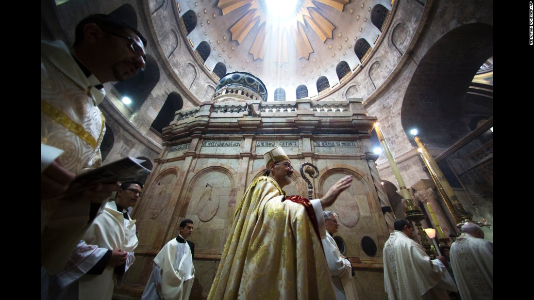 The Latin Patriarch of Jerusalem, Pierbattista Pizzaballa, walks with Christian clergymen holding candles during an Easter Sunday procession at the Church of the Holy Sepulchre in Jerusalem.