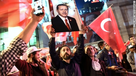 "A supporter of the ""yes"" brandishes a picture of Turkish president Recep Tayyip Erdogan among other supporters waving Turkish national flags during a rally near the headquarters of the conservative Justice and Development Party on April 16, 2017 in Istanbul after the initial results of a nationwide referendum that will determine Turkey's future destiny."