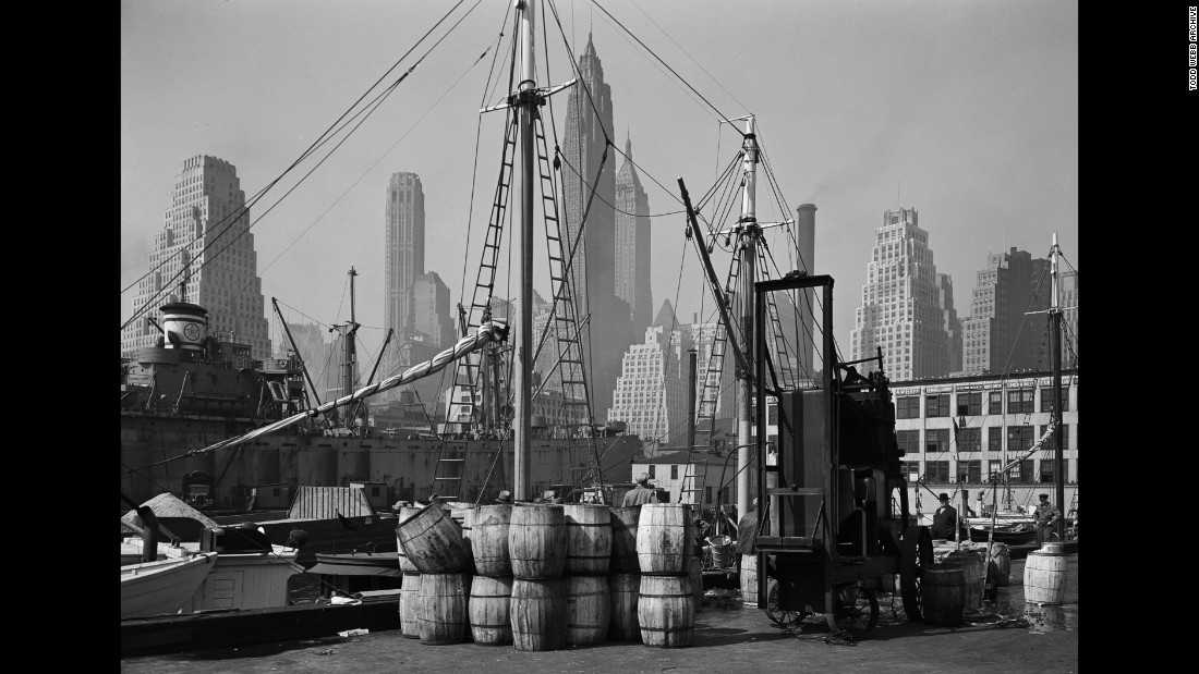 A view of the Fulton Fish Market in 1946. A ship sits in the foreground, while skyscrapers stand tall in the background.