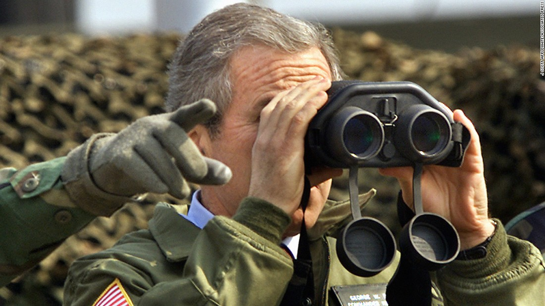 US President George W. Bush looks at North Korea from Observation Point Ouellette in the DMZ on Feb. 20, 2002. The president visited the zone to express his hope for communist North Korea to rejoin democratic South Korea someday.