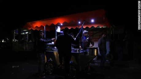 Customers visit a food stand in Gaza during an April 14 blackout.