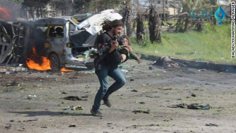 After a bombing in Syria, photographer Abd Alkader Habak runs towards safety with a child in his arms.