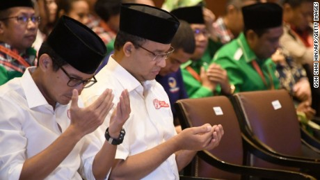Anies Baswedan (2L) and his running mate pray during an event in Jakarta on March 4.
