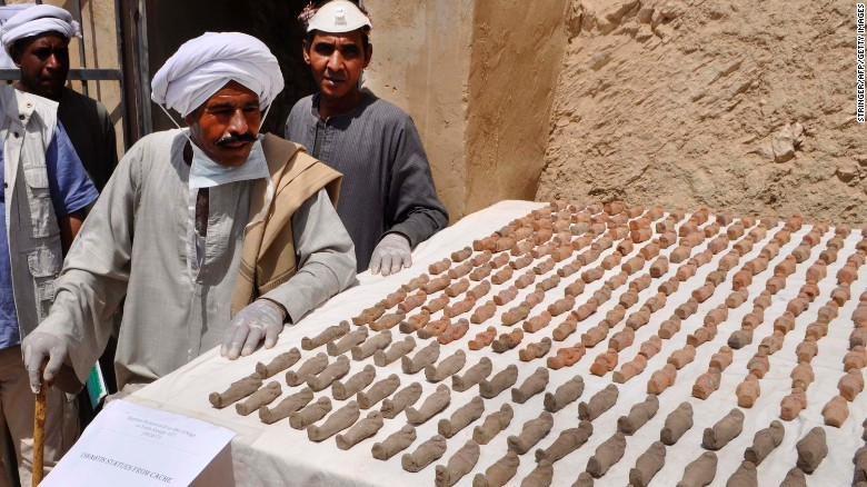 Members of the Egyptian archaeological mission eye funerary figurines known as ushabtis.