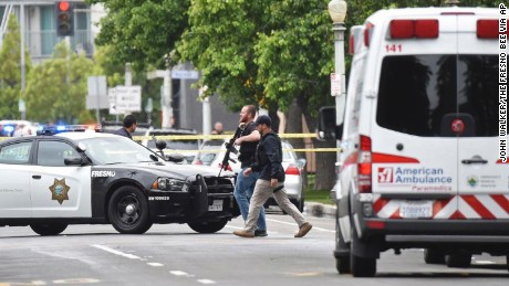 Police move near one of Tuesday's shooting scenes in downtown Fresno.