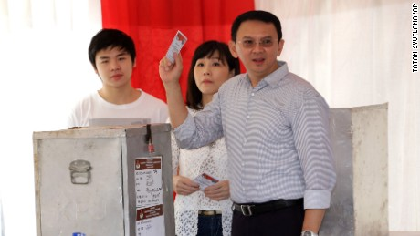 "Jakarta Governor Basuki ""Ahok"" Tjahaja Purnama who is seeking for his second term in office, his wife Veronica and son Nicholas, left, cast their ballot at a polling station during the runoff election in Jakarta, Indonesia, Wednesday, April 19, 2017. Residents of the Indonesian capital are electing a governor after a polarizing campaign that undermined Indonesia's reputation for practicing a tolerant form of Islam. (AP Photo/Tatan Syuflana)"