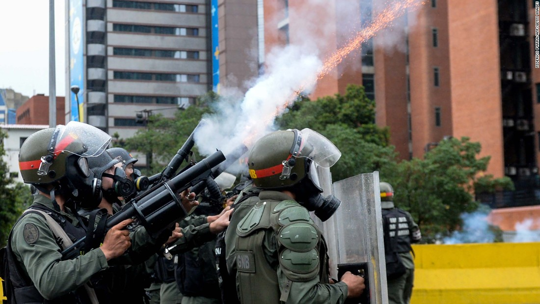 Riot police fire tear gas during clashes with protesters in Caracas, Venezuela.
