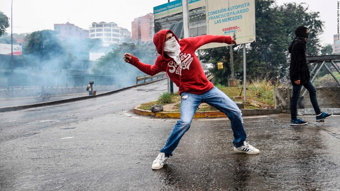An opposition supporter throws an object at riot police on Thursday, April 13, in Caracas, Venezuela. The opposition argues it can fix the country's failing economy, which in recent years has led to shortages of basic food and medicines.