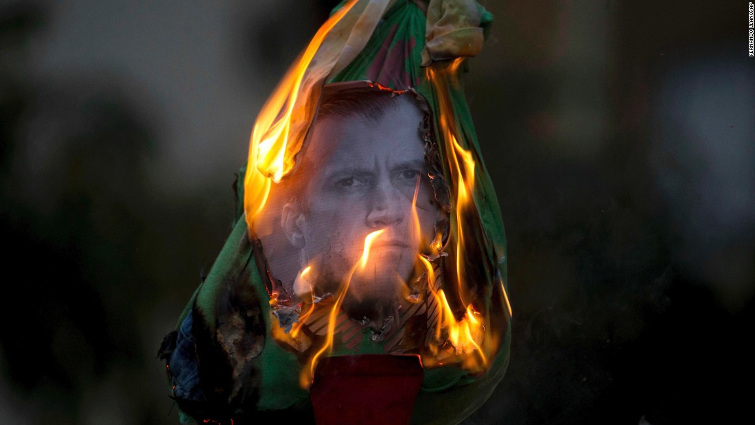 Opposition protesters burn an effigy of their country's vice president, Tareck El Aissami, during a protest in Caracas on Sunday, April 16.