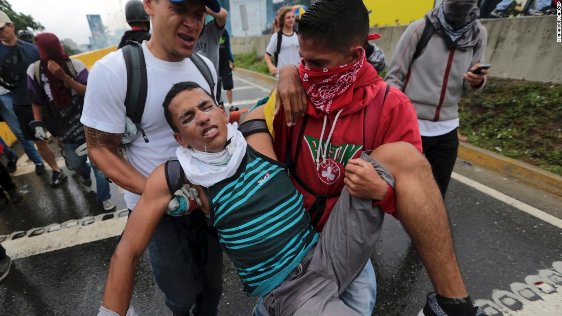 A protester suffering from the effects of tear gas is evacuated during a demonstration.