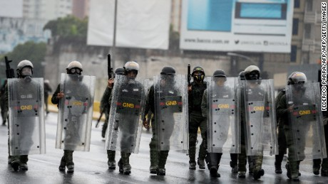Venezuelan National Guard personnel in riot gear face a march of opposition activists protesting against President Nicolas Maduro's government, in Caracas on April 13, 2017. A 32-year-old man died Thursday after being shot and wounded in a demonstration on April 11, becoming the fifth victim in the protests that began almost two weeks ago. Dozens of people have been injured and more than 100 arrested since April 6, according to authorities. / AFP PHOTO / FEDERICO PARRA        (Photo credit should read FEDERICO PARRA/AFP/Getty Images)