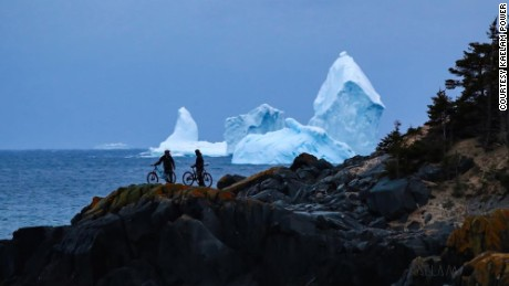 Mountain Bikers stop to look at icebergs drifting off the coast of Ferryland, Newfoundland, Canada on Tuesday, April 18, 2017.