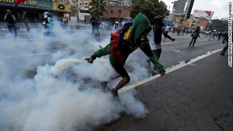 A demonstrator throws a tear gas canister back at the police during a rally against Venezuelan President Nicolas Maduro, in Caracas.