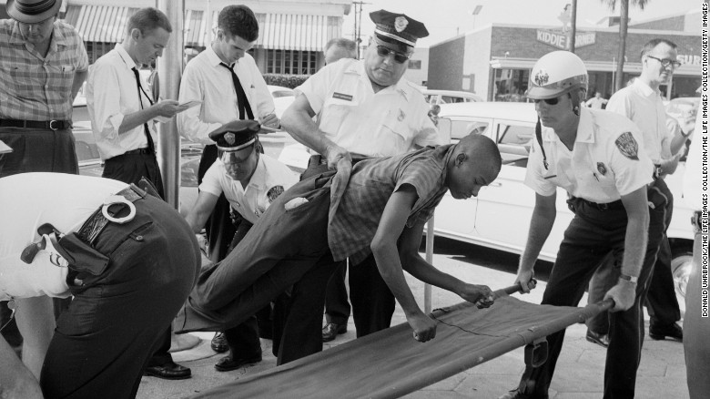 A protester being taken away by police at a civil rights demonstration.