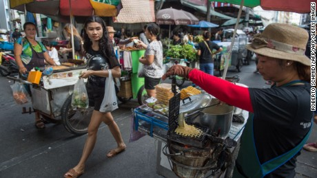 A vendor prepares a waffle on her street food cart at a local market in downtown Bangkok.