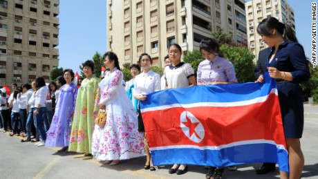 Young women hold a North Korean flag during a ceremony to name a park in Damascus after Kim Il-sung, August 31, 2015.