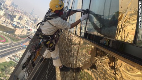 Workers from Megarme Rope Access installing the stainless steel gold cladding.