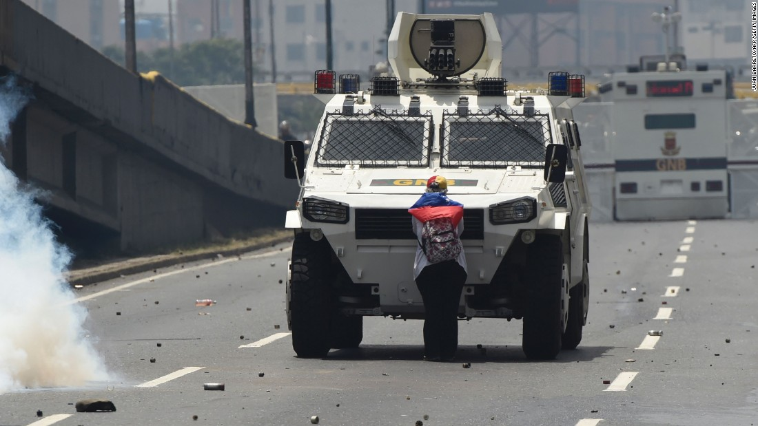 A demonstrator stands in front of an armored vehicle during protests in Caracas on Wednesday, April 19.