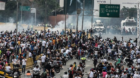 Demonstrators clash with the riot police during a protest against Venezuelan President Nicolas Maduro, in Caracas on April 20, 2017. Venezuelan riot police fired tear gas Thursday at groups of protesters seeking to oust President Nicolas Maduro, who have vowed new mass marches after a day of deadly unrest. Police in western Caracas broke up scores of opposition protesters trying to join a larger march, though there was no immediate repeat of Wednesday's violent clashes, which left three people dead. / AFP PHOTO / CARLOS BECERRA        (Photo credit should read CARLOS BECERRA/AFP/Getty Images)