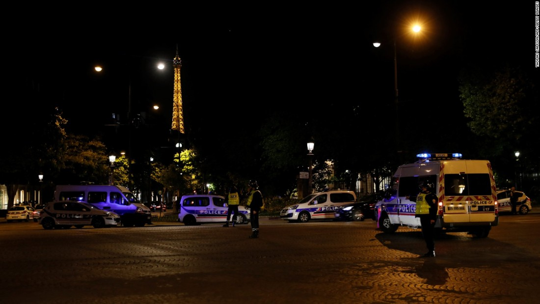 The Eiffel Tower is seen as police officers block the entrance to the Champs-Elysées.