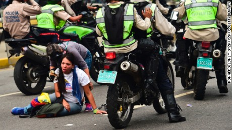 A demonstrator receives help during a protest against Venezuelan President Nicolas Maduro, in Caracas on April 20, 2017. Venezuelan riot police fired tear gas Thursday at groups of protesters seeking to oust President Nicolas Maduro, who have vowed new mass marches after a day of deadly unrest. Police in western Caracas broke up scores of opposition protesters trying to join a larger march, though there was no immediate repeat of Wednesday's violent clashes, which left three people dead. / AFP PHOTO / RONALDO SCHEMIDT        (Photo credit should read RONALDO SCHEMIDT/AFP/Getty Images)