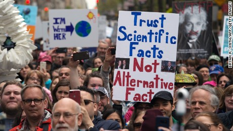 People hold up signs at a rally before the march for Science April 22, 2017 in New York. Scientists and their supporters across the globe are expected to march in the thousands Saturday amid growing anxiety over what many see as a mounting political assault on facts and evidence.