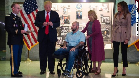 US President Donald Trump awards the purple heart to Sergeant First Class Alvaro Barrientos as first lady Melania Trump and Barrientos' wife Tammy stand by.