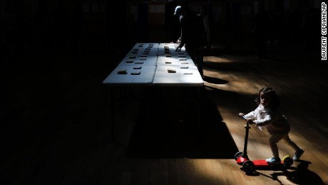 A girl rides a scooter as a man picks up ballots for the first round of the French presidential election in Lyon, France, Sunday April 23, 2017.