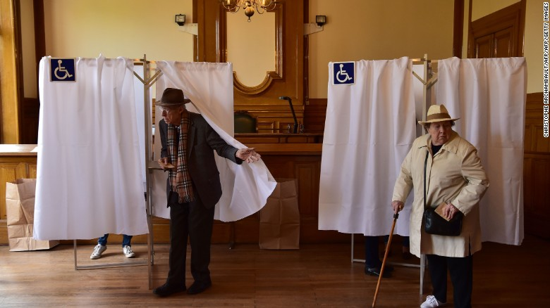 Voters leave their booths in the 7th district in Paris on Sunday to cast their ballots.