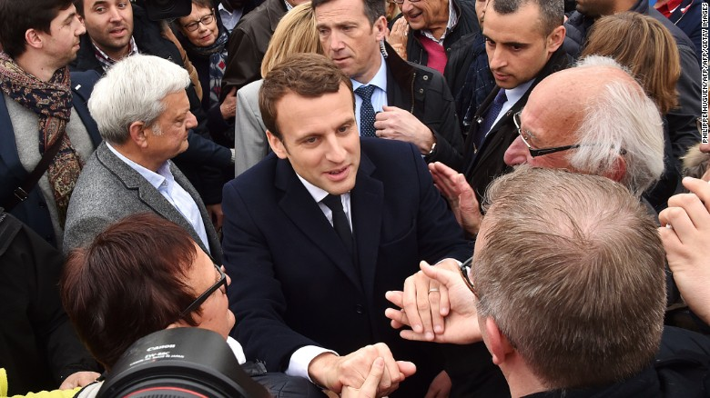 French presidential candidate for the En Marche! movement Emmanuel Macron shakes hands with supporters after casting his vote in Le Touquet.