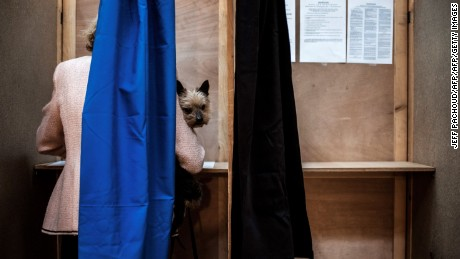 TOPSHOT - A woman with ger dog votes at a  polling station in Lyon, on April 23, 2017, during the first round of the Presidential elections. / AFP PHOTO / JEFF PACHOUD        (Photo credit should read JEFF PACHOUD/AFP/Getty Images)