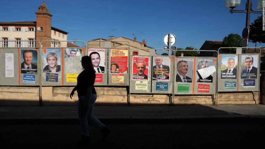 A woman walks past a wall of campaign posters in Villefranche-de-Lauragais.