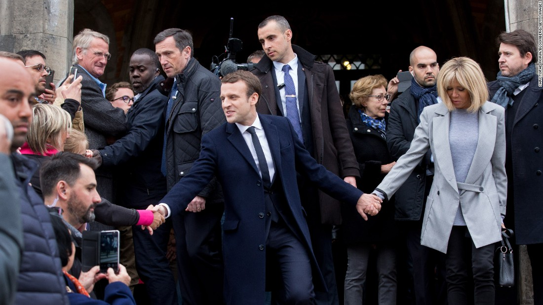 Macron and his wife, Brigitte Trogneux, greet supporters as they leave a polling station in Le Touque.