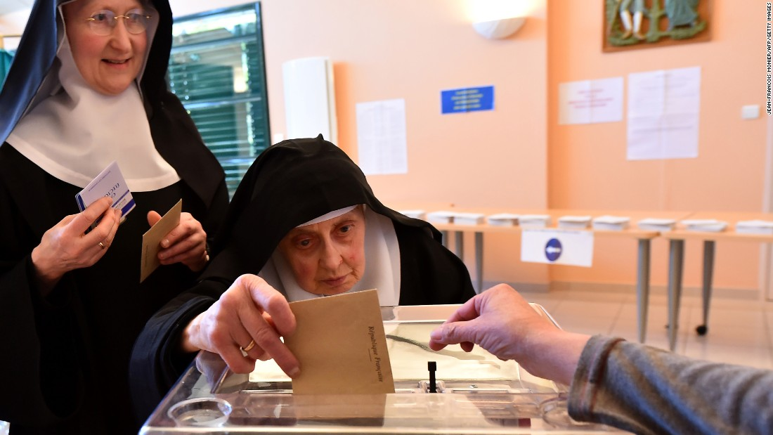 A Benedictine sister of the Sainte-Cecile Abbey casts her ballot at a polling station in Solesmes.