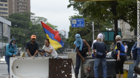 Venezuelan opposition activists set up a barricade to block an avenue in Caracas, on April 24, 2017. Protesters plan Monday to block Venezuela's main roads including the capital's biggest motorway, triggering fears of further violence after three weeks of unrest left 21 people dead. / AFP PHOTO / FEDERICO PARRA        (Photo credit should read FEDERICO PARRA/AFP/Getty Images)