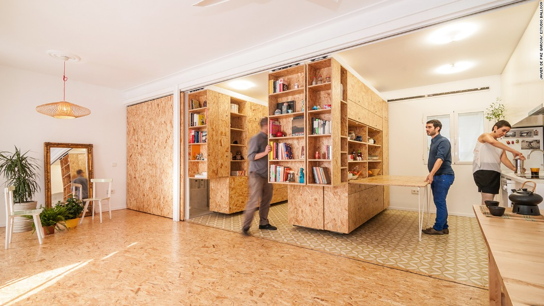 The movable shelving units in this apartment slide to convert this space from kitchen to bedroom.