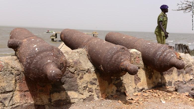 A police officer walks past cannons on Kunta Kinteh Island.